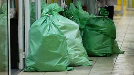 szakadt : Large green sealed mail bags in the corridor. Plastic fabric polypropylene bags filled with goods or boxes lie on the floor.
