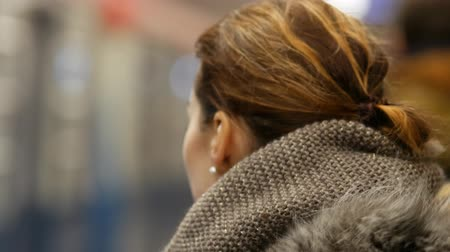ingázik : Young woman with flying hair in a winter jacket stands and wait on a subway platform in Moscow, Russia. Unrecognizable blurry people silhouettes on background. Crowd of people at rush hour in subway Stock mozgókép