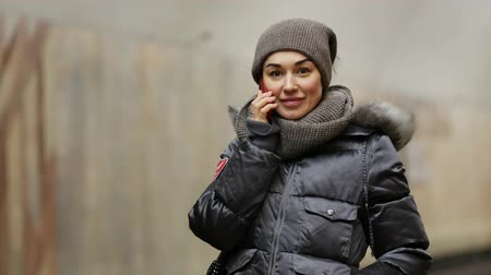 Girl with a phone in a winter jacket smiles on the platform of the metro station in Moscow, Russia. Young beautiful woman holds smartphone in her hand and looking to camera Filmati Stock