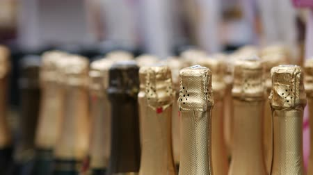 champagne bottles : Silver colored foil on the necks of sealed bottles of champagne on the eve of March 8, Womens Day holiday in the trading floor of the store. Unopened bubbly wine for celebration or romantic party.