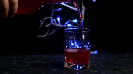 виски : New Years drink is poured into a transparent glass. Blue lights are lit behind. Dark background. Red wine.