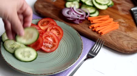 Slicing vegetables for a light salad. Vegetarian food. Healthy diet. Tomatoes, cucumbers, carrots and red onions. Salad sprinkled with sesame seeds and sprinkled with vegetable oil. Stok Video