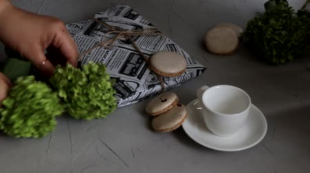 Preparing a composition with cookies and a cup of coffee for shooting. Nearby lies a wrapped present. On a light background.