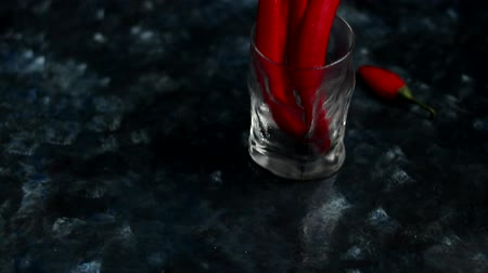 groene pepers : Bright red chili peppers in a transparent glass on a dark blue background. Color Trend Stockvideo