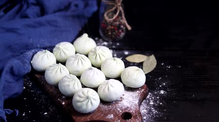 лучше : Frozen and raw henkali with spinach lie on a wooden board. Sprinkle with flour on top for better storage.