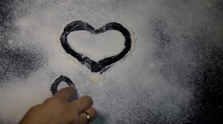 pegadas : Flour is sprinkled on the table. They draw a heart on it with a finger. Valentines Day. Dark marbled background. White flour.