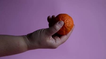 Tangerines in a hand on a pink background. Fresh vegetarian food. Healthy eating Stok Video