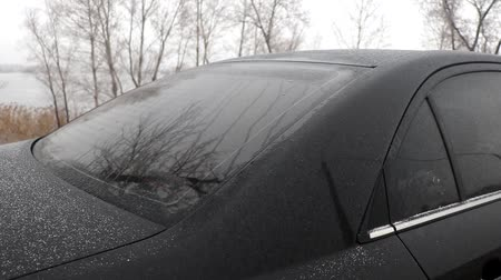 aveia : Winter nature. Frost is visible on the black car. Very little snow fell in January. Global warming. Environmental disaster.