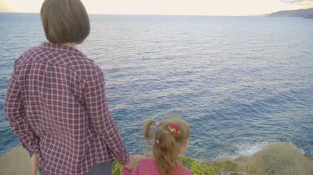crete : Mother and daughter standing on top of a mountain and looking at the sea. Sunset