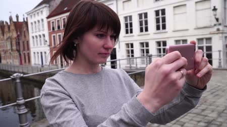 travelling : De vrouwentoerist neemt pictureson op smartphone in Brugge België. slow motion Stockvideo