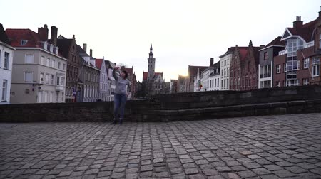 bruges : girl tourist makes selfi on a smartphone on a background of the city of Bruges Belgium Stock Footage