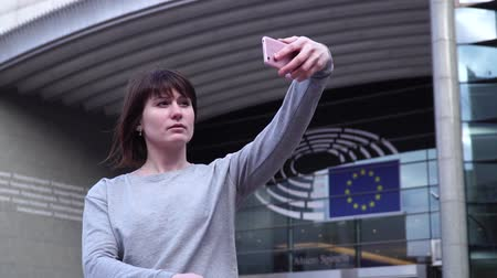 bruxelas : Woman tourist takes pictureson on smartphone near the European Parliament in Brussels. Belgium.
