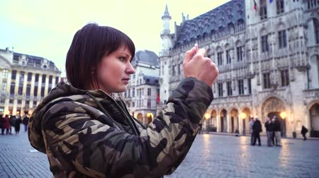 belga : Lady tourist takes pictures on Grand-Place in Brussels, Belgium.