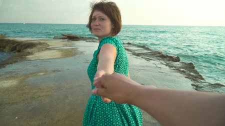 ma : Back view of woman holding hand of photographer asking to follow her while shaking hair and walking on rocks of seascape