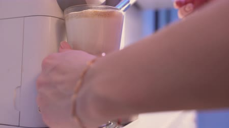 brew coffee : female hand picks up coffee from a coffee machine