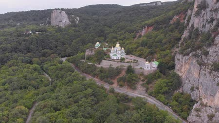 Aerial view: Beautiful Church with domes and crosses among green mountains Stock mozgókép