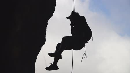 Climber silhouette descending the rock by rope at sky background