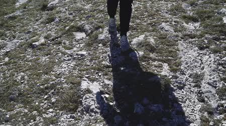 shadow and legs tourist walking high in the mountains