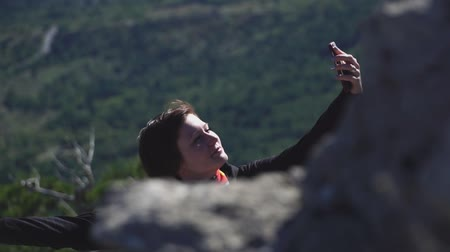 Tourist girl taking photo with smartphone on top of mountains Stock mozgókép