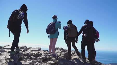 tırmanıcı : Tourists approach on top of the mountain and looking at the sea below, back view