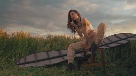 Pretty woman sitting in field with wings on her back and cigarette in her hands, resting after flight
