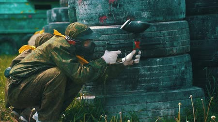 paintball : guy in camouflage with mask shoots with paintball gun