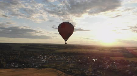 Aerial view: Hot air balloon in sky over field in countryside at beautiful sunset