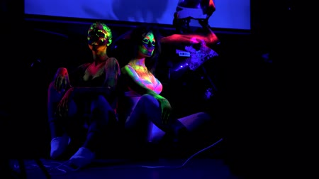 sahte : Two girls with futuristic fluorescent bodyart in ultraviolet light in night club Stok Video