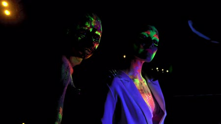 fluo : Two women with glowing fluorescent bodyart looking at camera
