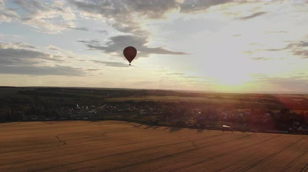 dirigível : Aerial view: Hot air balloon in sky over field in countryside at beautiful sunset