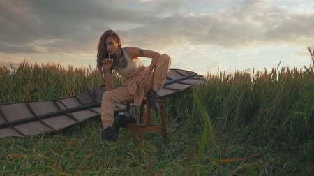 banquinho : lady with long hair sits on stool against brown glider wings
