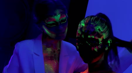 bizarre : Two girls with futuristic fluorescent bodyart in ultraviolet light in night club Stock Footage