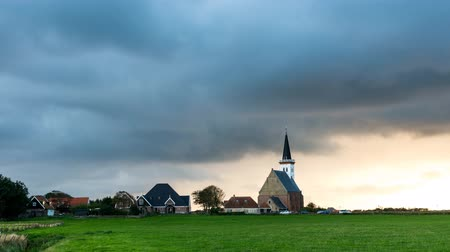 Den Hoorn, The Netherlands - September 9, 2015: Sunset and clouds at the small, white church of Den Hoorn on the island of Texel, The Netherlands.