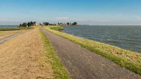 Uitdam, The Netherlands - September 11, 2015: Time lapse or bicycle path on a Dutch dike at transpiring with cyclists. Wideo