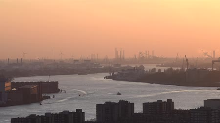 Nieuwe Maas in Evening Light with ships on the river, industrial areas and the harbor of Rotterdam in the Netherlands.