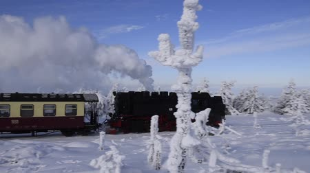 puffing : Brocken, Germany - February 5, 2018: Steam locomotive of the Harzer Schmallspurbahnen in wintertime with snow on the mountain Brocken in Saxony-Anhalt. Stock Footage