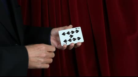 magia : Magician demonstrates sleight of hand playing card mastery.