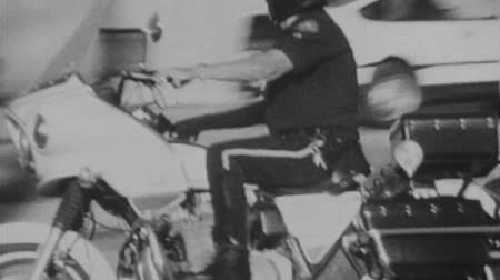 motor vehicle : LOS ANGELES, CALIFORNIA -  October 11, 1988:  Vintage super 8 footage of a Los Angeles Police Department motorcycle officer driving by in downtown Los Angeles.