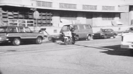 cannette : LOS ANGELES, CALIFORNIE - 11 sur Octobre 1988: Vintage super 8 images d'un agent de moto Los Angeles Police Department conduite par dans le centre de Los Angeles. Vidéos Libres De Droits