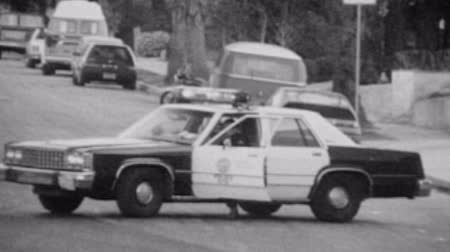 autó : Vintage 1988 super 8 footage of LAPD police car blocking a street in Hollywood, California.  Stock mozgókép