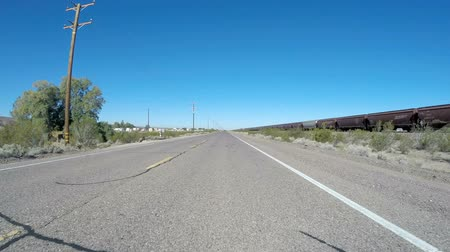 rota : BARSTOW, CALIFORNIA USA - March 27, 2015:  Driving time lapse of historic route 66 and train tracks in Californias Mojave desert.