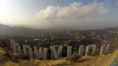 registrati : Los Angeles, California, USA - 22 aprile 2015: Lasso di tempo del famoso Hollywood Sign con compensazione nuvole del mattino in Griffith Park di Los Angeles.