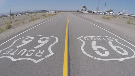 trace : Amboy California USA 7 mei 2015: Route 66 stoep teken in Californië de enorme Mojave woestijn. Stockvideo