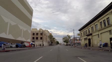 homeless : Los Angeles, California, USA - June 28, 2015:  Rear view driving shot of gritty skid row streets in downtown Los Angeles. Stock Footage