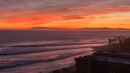 orange : Ventura, California, USA - December 7, 2015:  Colorful Pacific sunset zooming time lapse of surfers point beach in Ventura, California.