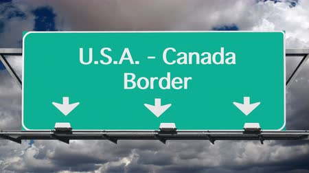 скрестив : USA Canada border crossing highway sign with time lapse clouds. Стоковые видеозаписи