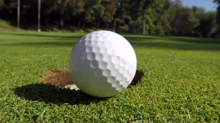 close up shot : Macro closeup of golfball being hit into hole.