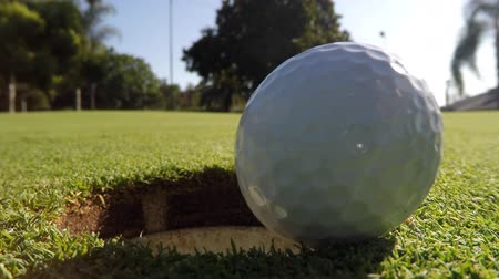 close up shot : Golf Ball Dropping into Hole Macro