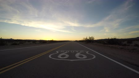 rota : Route 66 pavement sign driving shot after sunset in the California Mojave Desert.