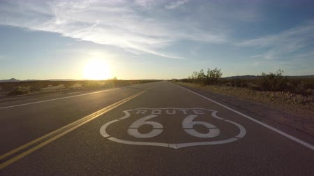 rota : Route 66 pavement sign sunset slow driving shot in the California Mojave Desert.